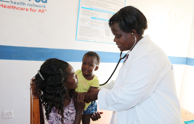 Alice Wasilwa, infirmière d'Etat et directrice de la maternité, s'occupe d'une mère et de son enfant lors d'une séance de consultation au centre de santé Méthodiste de Kopanga, au Kenya. La clinique Méthodiste Unie dessert environ 1 000 patients par mois et offre des services de maternité, y compris des soins prénataux et postnataux. Photo de Gad Maiga, UM News.