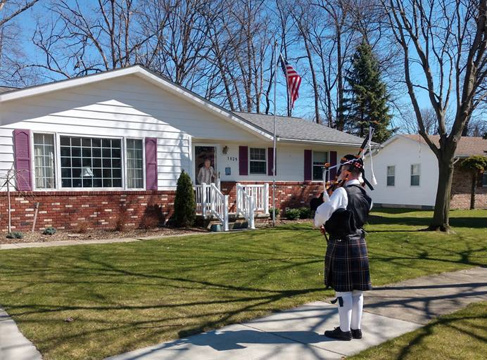 Wyatt Clarke, 15, plays bagpipes outside the house of a neighbor in Marysville, Michigan. The teen has been playing bagpipes to provide entertainment and solace to residents self-isolating during the coronavirus pandemic. Photo courtesy of Marysville United Methodist Church.