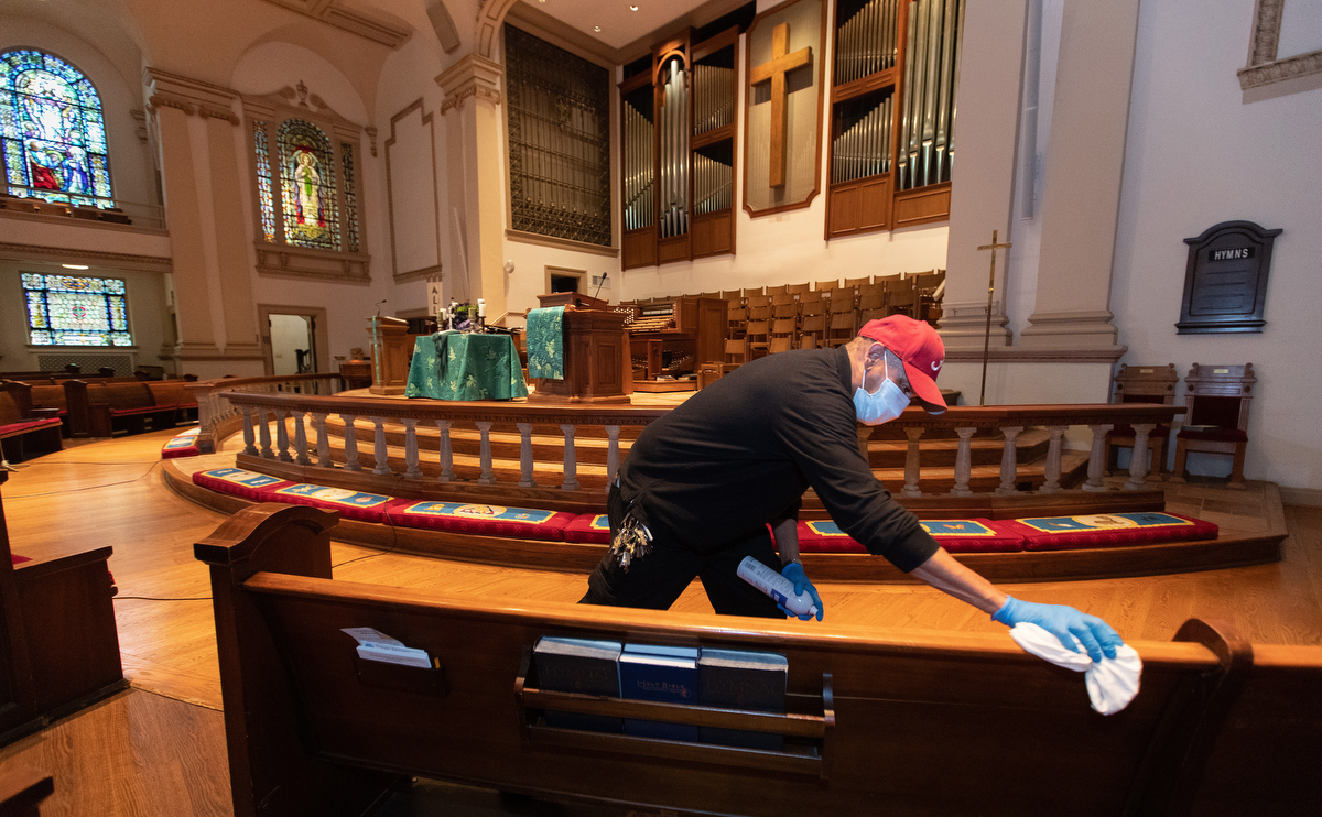 """Custodian James Jimmerson disinfects pews to prevent any possible spread of the coronavirus at Belmont United Methodist Church in Nashville, Tenn. on Sunday, May 10, 2020, after online worship, which was recorded in the sanctuary. As churches consider returning to in-person worship, cleaning measures are one of many factors leaders will need to consider. """"I believe my job, my part in this, is to make sure people are safe in here,"""" Jimmerson said. Photo by Mike DuBose, UM News."""