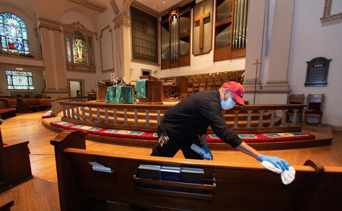 """O zelador James Jimmerson desinfeta os bancos para impedir qualquer possível propagação do coronavírus na Igreja Metodista Unida de Belmont, em Nashville, Tennessee, no domingo, 10 de maio de 2020, após o culto on-line, que foi registrado no santuário. Como as igrejas consideram retornar ao culto pessoalmente, as medidas de limpeza são um dos muitos fatores que os líderes precisam considerar. """"Acredito que meu trabalho, minha parte nisso, é garantir que as pessoas estejam seguras aqui"""", disse Jimmerson. Foto de Mike DuBose, Notícias MU."""