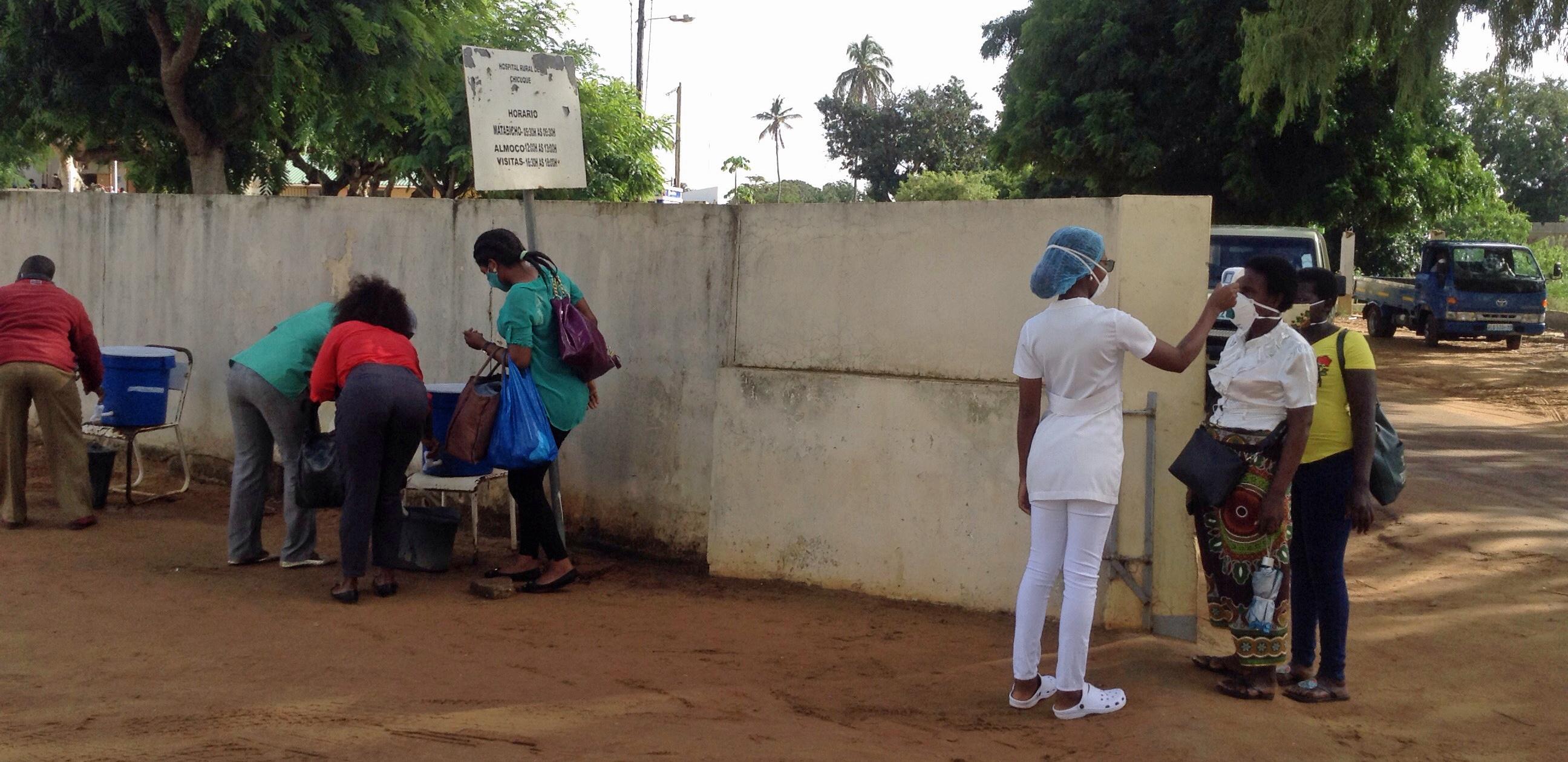 Utentes do Hospital Rural de Chicuque, sendo testados a temperatura na entrada principal do hospital e depois recomendados a lavarem as mãos. Chicuque, foto de António Wilson.