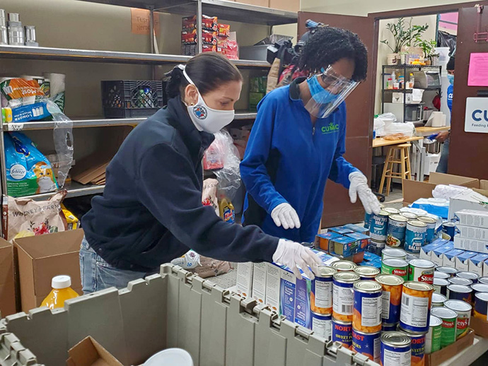 "Tammy Murphy (left), the First Lady of New Jersey, helps Kay Ann Foster pack food boxes for mothers and children during a May 14 stop at CUMAC, a food organization in Paterson, N.J., that is one of 23 designated ""Hope Centers"" of the United Methodist Greater New Jersey Conference. Photo courtesy of CUMAC."