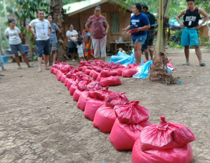 United Methodists, led by the Rev. Recto Baguio, superintendent of the Mindanao Central East District, distribute food to communities struggling during the coronavirus pandemic in the Philippines. The relief packs include rice, canned goods, noodles, sugar, salt, dried fish and soap. Photo courtesy of the Rev. Recto Baguio.