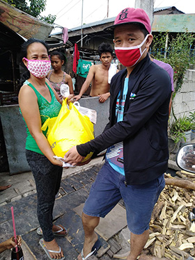 Louie David (right), United Methodist Young Adults vice president, delivers food relief to families in the Balete barangay, inside Hacienda Luisita in Tarlac City, Philippines. Photo courtesy of the Rev. Marlon Magno.