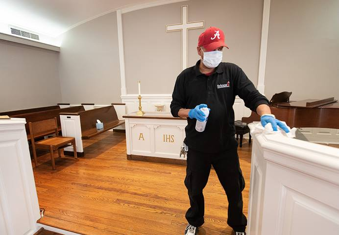 Custodian James Jimmerson disinfects the chancel area to prevent any possible spread of the coronavirus at Belmont United Methodist Church in Nashville, Tenn., on Sunday, May 10, 2020, after online worship, which is recorded in the chapel. Bishops are setting guidelines, including standards for cleaning, and recommending what they think are appropriate times for the churches in their conference to reopen. Photo by Mike DuBose, UM News.