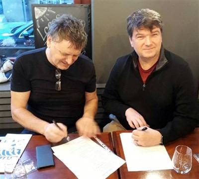 Hicks firmando un contrato con Miroslav Pycha, gerente de la radio. Foto cortesía de la Conferencia Anual de Holston.