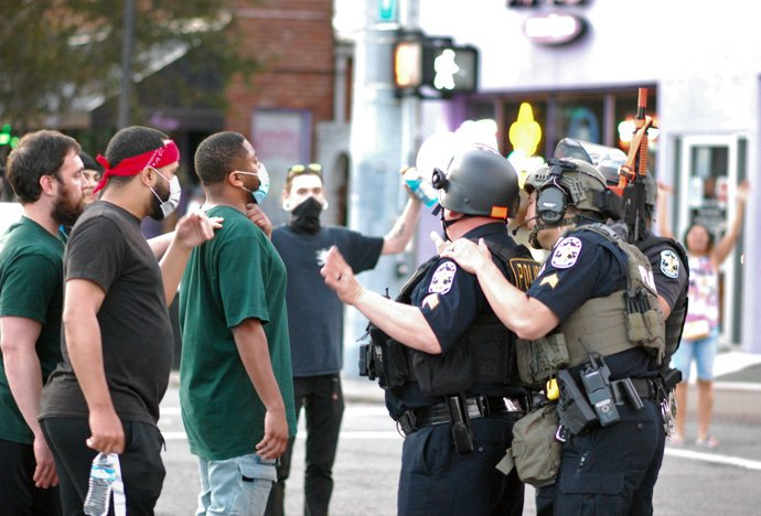 Men talk with police in downtown Louisville, Kentucky, during four days of protests May 28-31 over the killings by police of Breonna Taylor in Louisville and other African Americans. One person was killed and seven injured during the protests in Louisville. Photo by Cathy Bruce, courtesy of the Kentucky Conference.