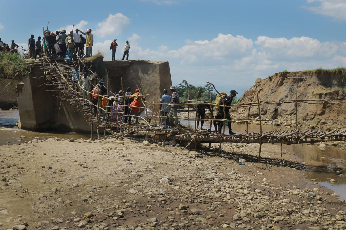 People walk over a wooden bridge built by United Methodist Men of Sange after the original bridge was washed away by mid-April flooding in Uvira, Congo. Photo by Philippe Kituka Lolonga, UM News.