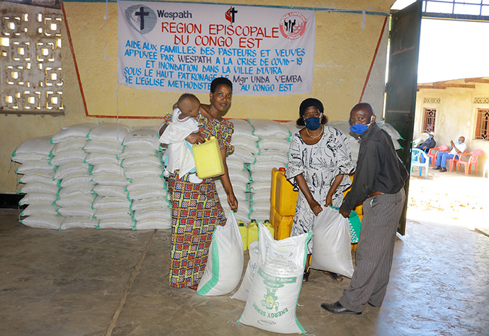 The Rev. Simon Kombi Ramazani (right), connectional ministry director for the Kivu Conference, gives food to a widow whose husband died following flooding in Uvira in April. Wespath Benefits and Investments, the United Methodist pension agency, provided food relief to pastors and widows in the Uvira District. Photo by Philippe Kituka Lolonga, UM News.