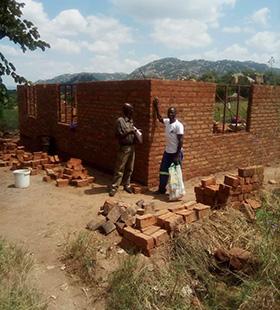 L'ingénieur Cassian Mutsambiwa et le bâtisseur Pamganai Ziwewe se tiennent devant la nouvelle maison de quatre chambres que l'Église Méthodiste Unie construit pour Elizabeth Hwatira et sa famille à Bikita, Masvingo. La maison de cette famille a été détruite par le cyclone Idai en 2019. Photo de Chenayi Kumuterera, UM News.