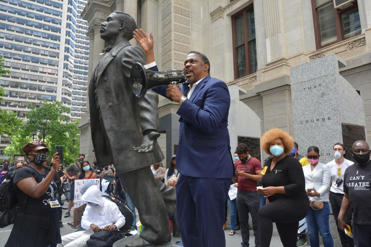 The Rev. Gregory Holston speaks during a May 31 demonstration at Philadelphia City Hall in honor of George Floyd. Holston, a United Methodist pastor and adviser to Philadelphia's district attorney, stands beside a statue of slain voting rights activist Octavius Catto. Photo by Samaria Bailey, Philadelphia Tribune.