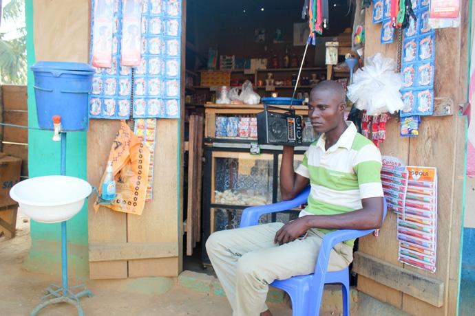 Albert Ngandji, président de la Jeunesse Pour Christ de l'église Méthodiste Unie francophone Bethlehem de Tokolote écoutent une prédication diffusée en direct à la radio. La radio est l'un des moyens de communication les plus utilisés en RDC. Photo de Chadrack Londe.