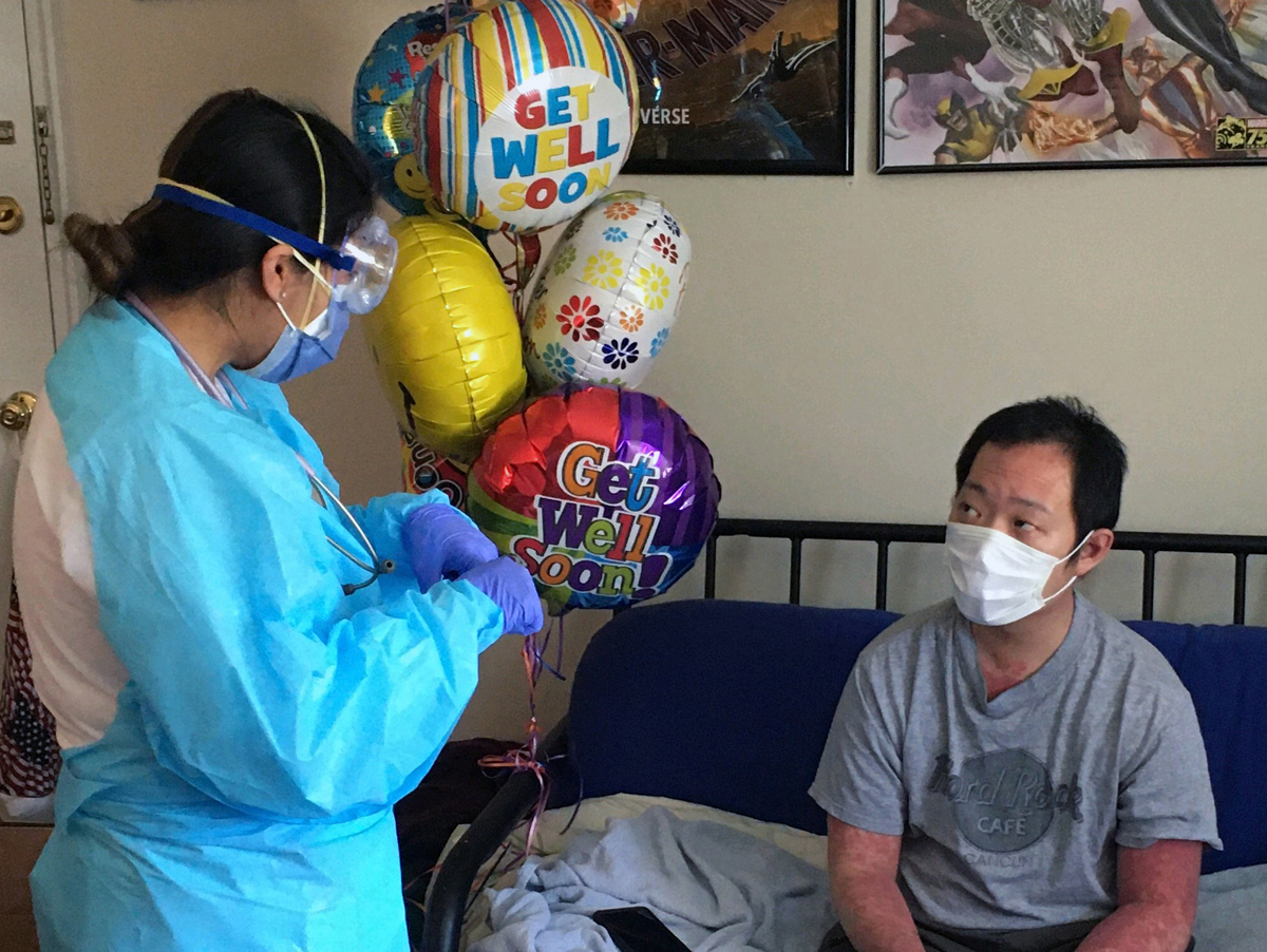 Chris Yuen (right) gets a bouquet of balloons during his hospital stay for the coronavirus. Yuen, a 32-year-old member of Midland Park United Methodist Church in New Jersey, spent about 20 days on a ventilator. Doctors and nurses lined the hall to cheer when he went home on April 22, after nearly a month's hospitalization. Photo courtesy of Chris Yuen.