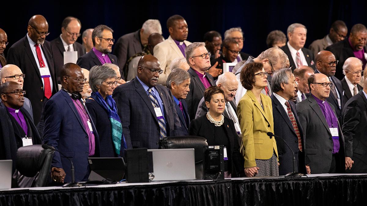 Os bispos juntam as mãos em oração durante a Conferência Geral da Metodista Unida de 2019 em St. Louis. Na maioria dos casos, os bispos que planificavam aposentar-se este ano ou no início do próximo ano ficam até a realização de novas eleições para os bispos. Foto de arquivo de Kathleen Barry, UM News.