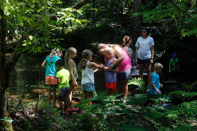 Campers and counselors explore the creek at Cedar Crest Camp in Lyles, Tenn., in 2017. Cedar Crest, like many other United Methodist camps, has suspended operations this summer due to COVID-19. File photo by Kathleen Barry, UM News.