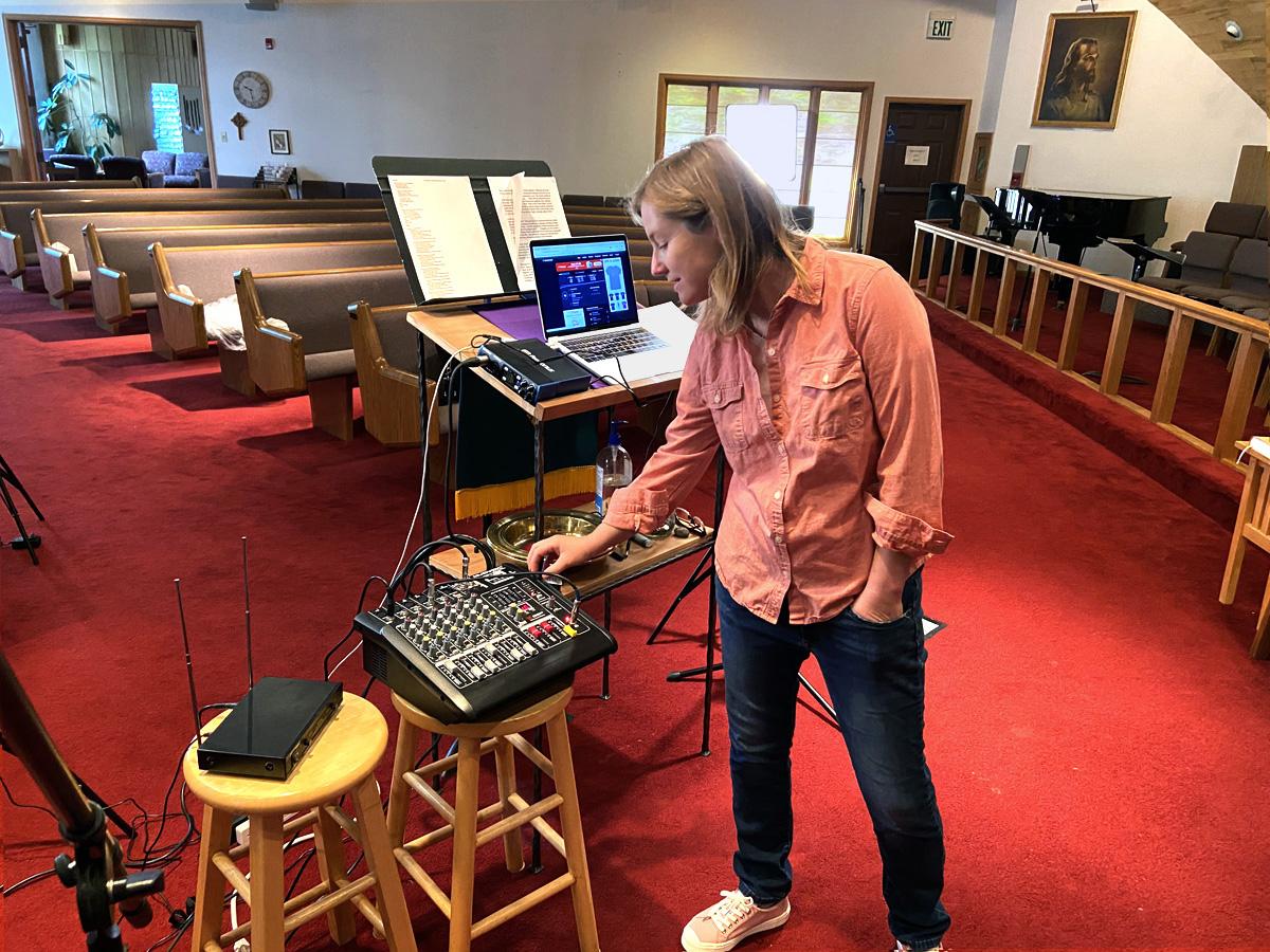 Molly Fiore, pastora de la IMU Eagle Valley en Eagle, Colorado, revisa los controles en la cónsola de sonido cerca del púlpito de la iglesia. Con las iglesias cerradas debido al COVID-19, los/as trabajadores/as de la tecnología de información y los/as pastores/as tuvieron que mejorar sus habilidades tecnológicas para conectarse con las congregaciones. Foto de Matt Miller, cortesía de la IMU Eagle Valley.