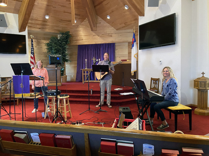 (From left) Pastor Molly Fiore, guitarist Matt Miller and keyboard player Jenny Roussel sit among audio and recording equipment in United Methodist Church of Eagle Valley in Eagle, Colo. Photo courtesy of United Methodist Church of Eagle Valley.