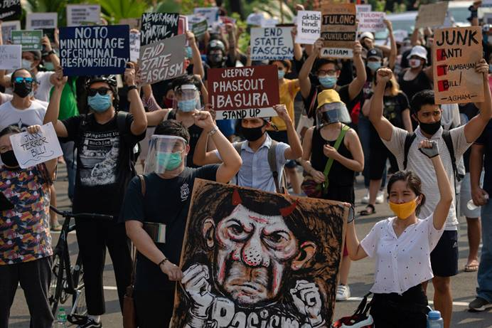 Protesters in Manila raise placards calling on legislators to scrap the anti-terror bill that has drawn concern from human rights activists who fear it could be used to suppress free speech and harass those who challenge President Rodrigo Duterte. Photo by REUTERS/Eloisa Lopez.