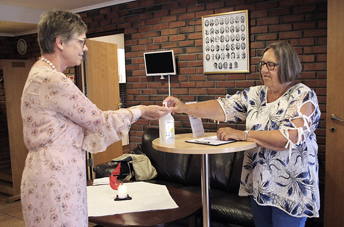 Elizabeth Moe Skreosen, chairwoman of The United Methodist Church Porsgrunn in Norway, is welcomed by fellow church member Kari Palmgren with an offer of hand sanitizer. Photo courtesy of The United Methodist Church Porsgrunn.