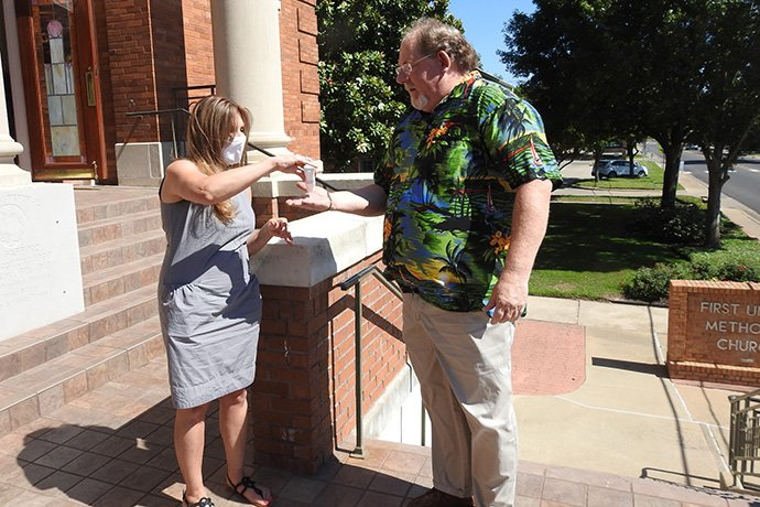 Lisa Lantz applies hand sanitizer for Stephen Morgan before a June 14 worship service at First United Methodist Church of Sulphur Springs, Texas. The church resumed in-person worship that day, taking various safety measures because of the coronavirus pandemic. Photo by Sam Hodges, UM News.