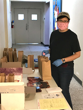 The Rev. Raquel Feagins of La Trinidad United Methodist Church in San Antonio prepares bags that include the Upper Room devotions and communion elements for about 220 people. People pick up the packages curbside during the time of online worship. Photo by the Rev. John Feagins of La Trinidad United Methodist Church.