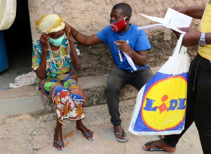 Uma anciã da comunidade é auxiliada a por máscara. Malange, foto de Gelson Carlos.