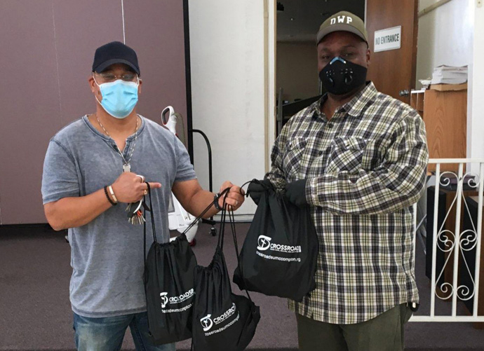Saun Hough (left), associate pastor at Crossroads United Methodist Church in Compton, Calif.,  hands reentry hygiene kits to Jerrel McCoy, lead community health worker at SHIELDS For Families. The church mobilized to create 3,500 kits for citizens released from prison by the state of California. Photo courtesy of Crossroads United Methodist Church.
