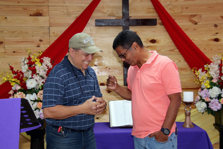 O membro Francisco Rangel (à esquerda) e o Rev. Angel Santiago alcançam um espaço de armazém que foi convertido no novo santuário da Primeira Igreja Metodista da Ressurreição em Ponce, Porto Rico, depois que danos causados por terremotos forçaram o fechamento do santuário da congregação a um quarteirão de distância. Foto por Tita Parham, FUMF.