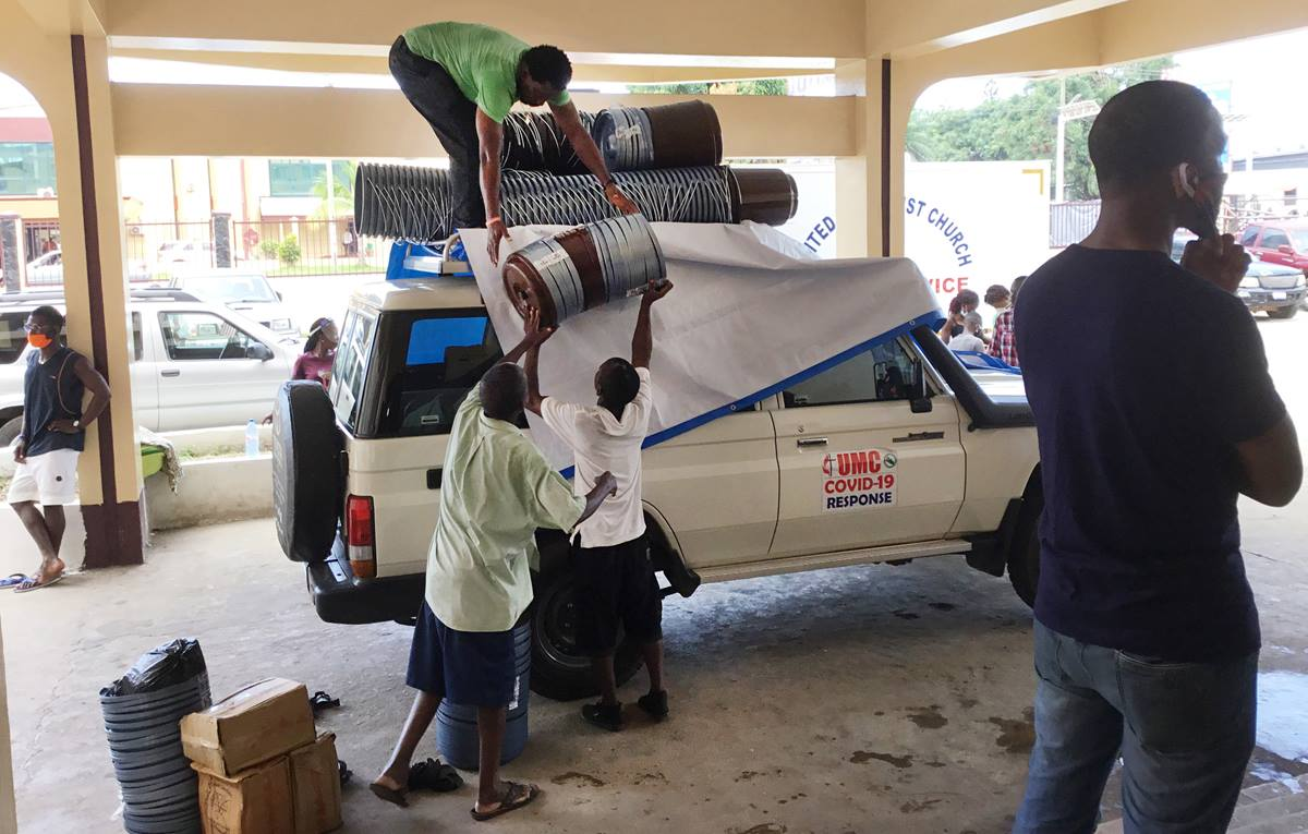 Workers with the church's Department of Community Services load supplies onto a vehicle to deliver to rural Liberia. The food relief — supported by UMCOR and other global partners — is part of the efforts of The United Methodist Church's Anti COVID-19 Taskforce. Photo by E Julu Swen, UM News.