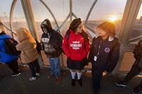 Ruth Moreno (in red sweatshirt) and her brother, Lino, make their way to school as the sun rises behind them on the Santa Fe Bridge over the Rio Grande in Juárez, Mexico, in November 2019. They made the two-hour cross-border journey each school day to attend the United Methodist Lydia Patterson Institute in El Paso, Texas, before in-person classes were halted due to the COVID-19 pandemic. File photo by Mike DuBose, UM News.