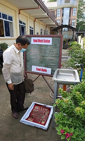 Bishop Rodolfo A. Juan inspects a hand-washing and foot bath station outside Kabacan Central United Methodist Church in North Cotabato, Philippines. Photo courtesy of Bishop Rodolfo A. Juan.