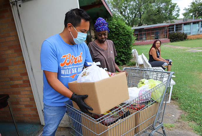 A volunteer from Tulsa Indian United Methodist Church loads up food boxes in a shopping cart so participants can take them home to a nearby apartment complex. Tulsa Indian United Methodist Church operates a food bank on the last Friday of the month. Photo by Ginny Underwood, UM News.