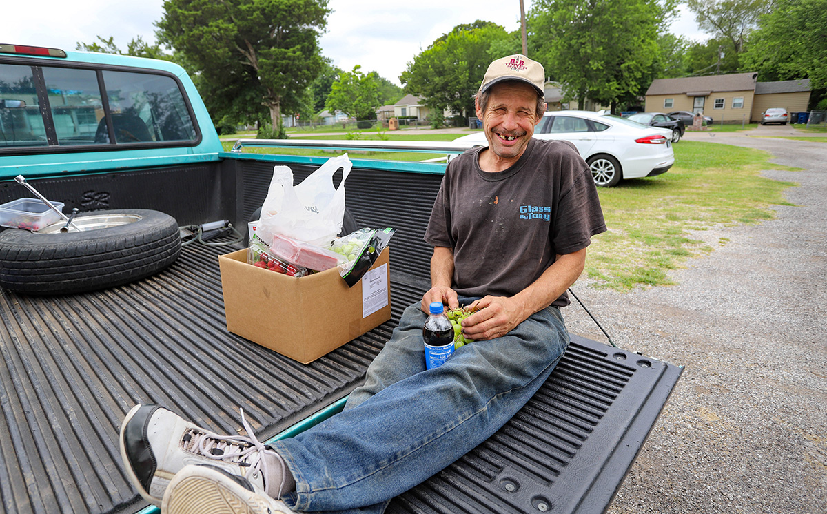 Michael, a food pantry participant, holds fresh grapes and other produce provided by Tulsa Indian United Methodist Church. He said he rarely has access to fresh fruit. Photo by Ginny Underwood, UM News.