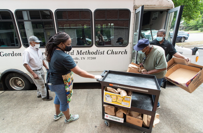 The Rev. Paula Smith (second from left) steadies a cart while volunteers Tim Morgan (in green t-shirt) and Richard Wilson load box lunches for distribution through the Hands of Hope food security program at Gordon Memorial United Methodist Church in Nashville, Tenn. At left is volunteer Matthew Job, 80, who drives the church van for the program. Photo by Mike DuBose, UM News.