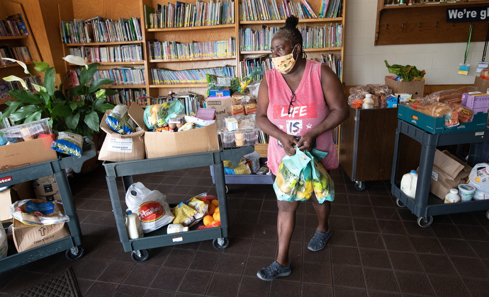 Volunteer Dee Farr carries donated food for a client at the Branch of Nashville emergency food assistance program at Antioch (Tenn.) United Methodist Church. The program received a Sheltering in Love grant from the United Methodist Committee on Relief to assist vulnerable communities during the COVID-19 pandemic. Farr said she once received assistance from the program and has been returning regularly to volunteer. Photo by Mike DuBose, UM News.