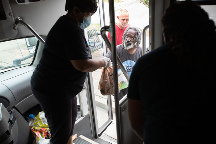The Rev. Michelle Wilson (left) offers sack lunches from the door of the church van as part of the Hands of Hope food security program at Gordon Memorial United Methodist Church in Nashville, Tenn. Photo by Mike DuBose, UM News.