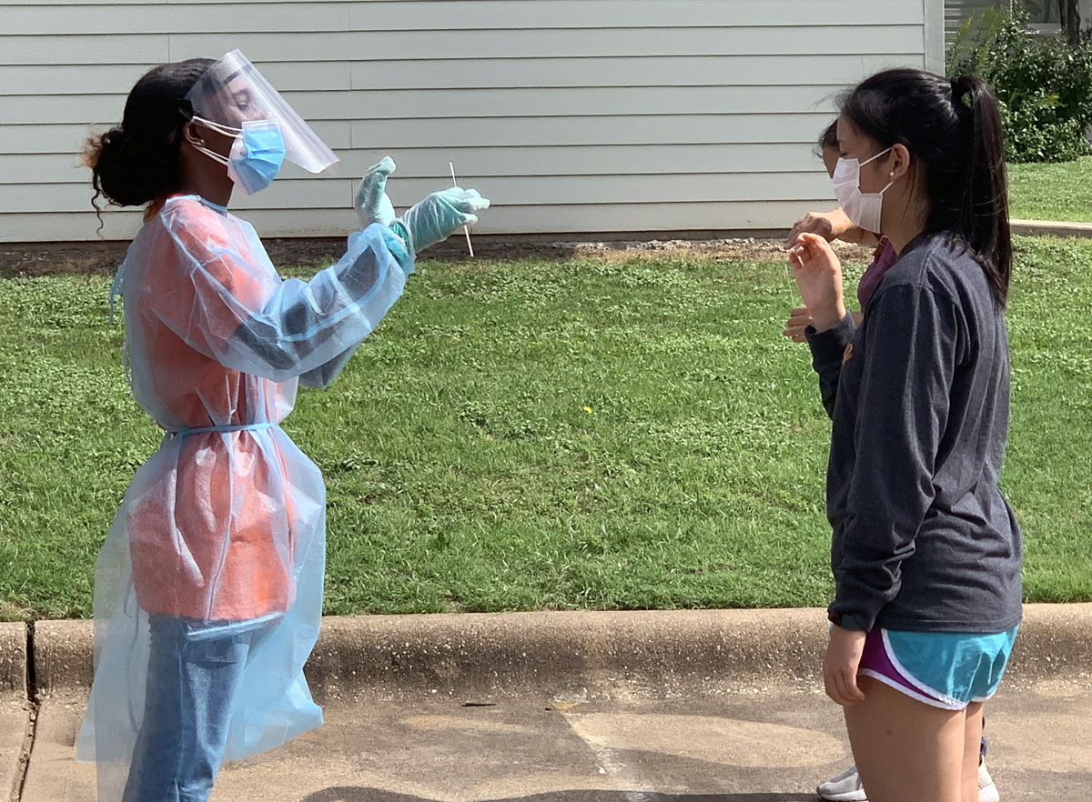 A woman in protective gear holds out a swab to a woman who has come for COVID-19 testing at Cochran Chapel United Methodist Church in Dallas, Texas. Cars lined up early for the June 29 opportunity. Photo by Matt Jacob, North Texas Conference.