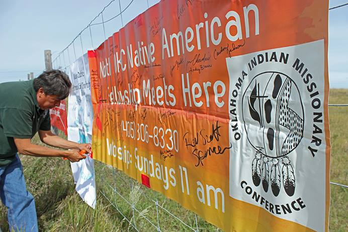 The Rev. David Wilson, conference superintendent of the Oklahoma Indian Missionary Conference of the United Methodist Church, attaches banners from his conference to a fence near the Dakotas Access Pipeline, Highway 1806, near Cannon Ball, N.D. File photo by Dave Stucke, Dakotas Conference.