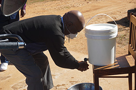 Naboth Makunike, the building committee chairperson for Mutasa Central United Methodist Church of Mutasa Nyanga District, washes his hands from a 20-liter bucket of sanitized water at a church gathering at Ehnes Memorial United Methodist Church. Photo by Kudzai Chingwe, UM News.