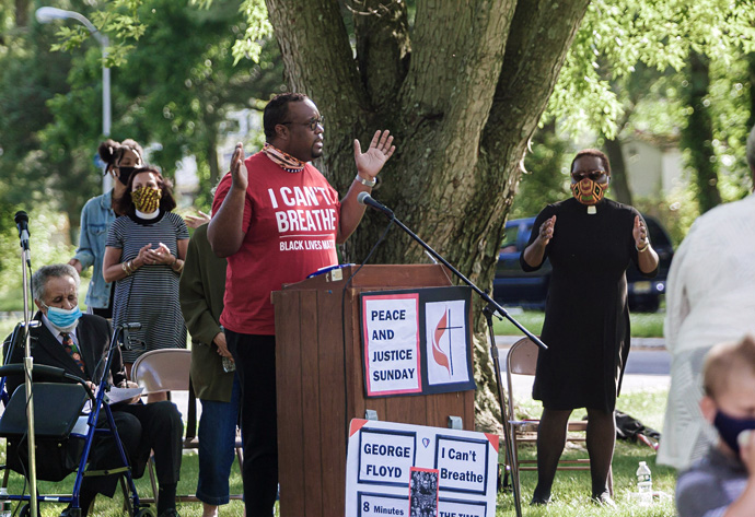Lan Wilson (center), director of worship for the Greater New Jersey Conference, addresses those gathered during a Black Lives Matter rally June 7 in Willingboro, New Jersey. Seated behind Wilson is the Rev. Gilbert Caldwell, who also spoke. The Rev. Tanya Bennett, chairperson of GNJ's Board of Church and Society (behind Wilson in striped dress) and the Rev. Vanessa Wilson, chairperson of GNJ's Commission on Race and Religion (far right in black dress), listen. Photo by Aaron Wilson Watson.