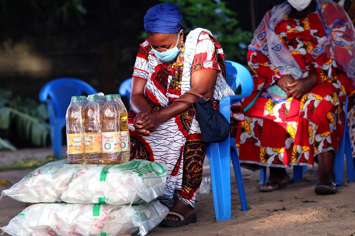 Akou Logbo a la tête baissée pendant que l'Evêque Benjamin Boni prie pour les victimes des inondations à Abidjan, en Côte d'Ivoire, et de la pandémie de la COVID-19. Elle fait partie des 300 veuves dont les activités ont été impactées par l'isolement lié à la COVID-19. Elles ont reçu des dons en vivres et non-vivres d'une valeur de 30 000 dollars, financés par UMCOR, l'agence d'assistance humanitaire de l'Eglise. Photo de Isaac Broune, UM News.