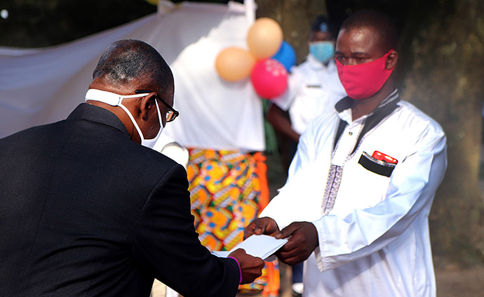 Bishop Benjamin Boni gives an envelope of cash money to Seydou Bakayoko, who lost five relatives in the floods in Abidjan. Each bereaved family received $100 for each person who died during a special ceremony held in Anyama, Côte d'Ivoire. Photo by Isaac Broune, UM News.