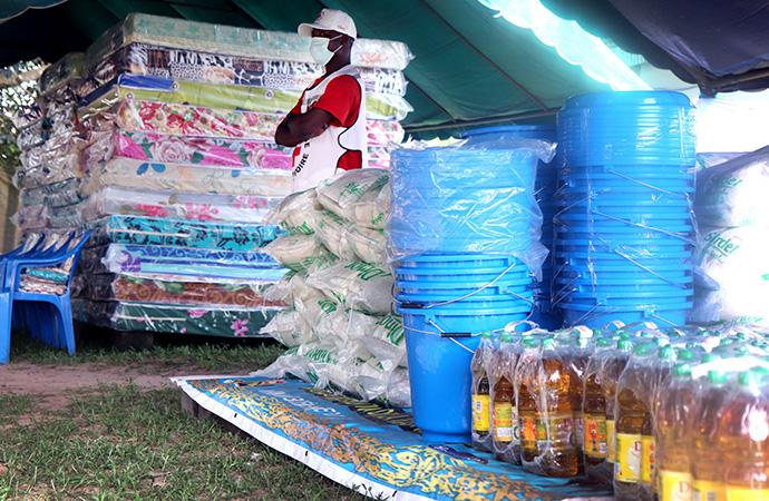 Un volontaire de la Croix-Rouge se tient près des dons de vivres et non-vivres d'une valeur de 30 000 dollars financés par UMCOR pour soutenir les victimes des inondations et de la pandémie de la COVID-19 dans la région du Grand Abidjan. La cérémonie de distribution a eu lieu le 5 juillet à Anyama. Photo de Isaac Broune, UM News.