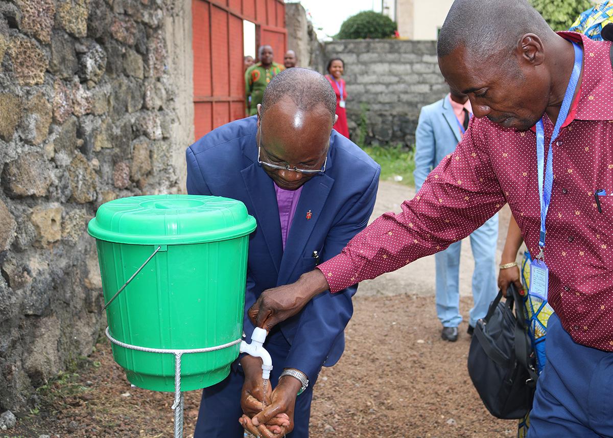 Pendant l'épidémie d'Ebola, l'Evêque de la Région de l'Est du Congo, Gabriel Yemba Unda, se lave les mains pendant la conférence annuelle du Kivu en Juin 2019. Il est aidé par le Révérend Jean-Paul Omole, Surintendant du district de Goma. Photo de Chadrack Londe, UM News.