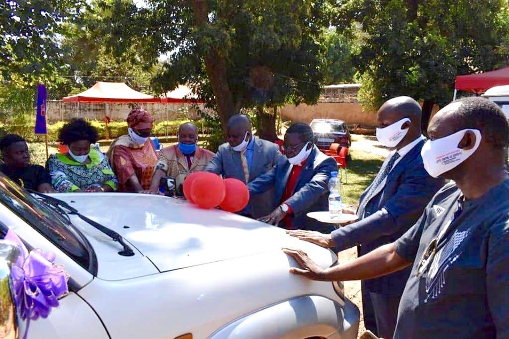 L'Evêque Kasap Owan de la Région Episcopale du Sud Congo/Zambie (au centre) et des membres de son cabinet prient pour le véhicule offert par Coalice Mwamba, un Méthodiste Uni, au Département d'Evangélisation de la Région Episcopale. Photo de John Kaumba, UM News.