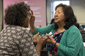 The Rev. Josephine Deere, right, blesses fellow Connectional Table member Benedita Penicela Nhambiu during a service of baptism remembrance on April 3, 2019 at the Connectional Table meeting in Nashville, Tenn. File photo by Kathleen Barry, UM News.