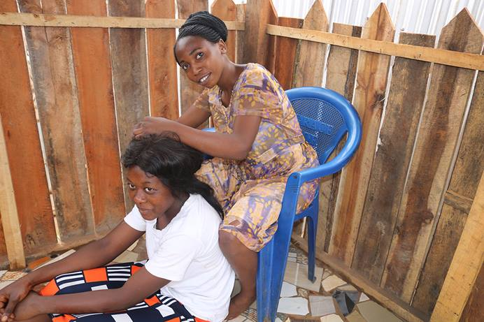 Marie Aganze, 19, fixes Pauline Laini's hair at her salon in Bukavu, Congo. Aganze, who was forced to drop out of school at age 10, received skills training from The United Methodist Church in East Congo. Photo by Philippe Kituka Lolonga, UM News.