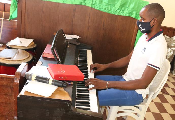 Mestrinho Jairo Fontoura da Silva tocando piano durante o culto de reabertura. Malange, foto de João Gonçalves Nhanga.