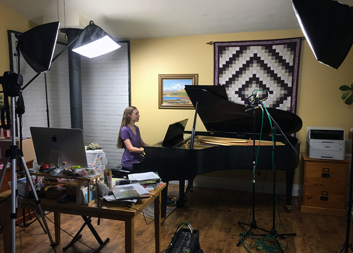 Freya Wardlaw-Bailey, accompanist for St. John United Methodist Church in Anchorage, Alaska, plays the piano amid equipment used for making virtual choir videos. Her husband, James Wardlaw-Bailey, leads the church's choir program and does the video editing, spending three or four hours per anthem. Photo courtesy of James Wardlaw-Bailey.