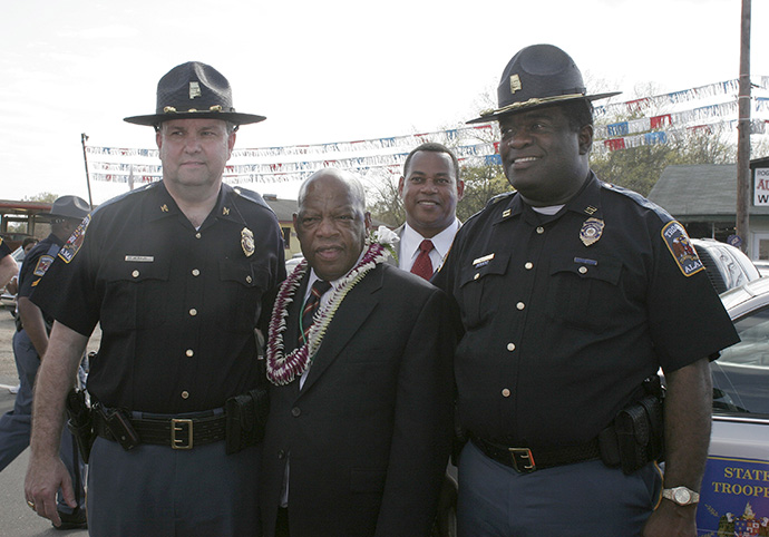 Two Alabama state troopers pose with Congressman John Lewis following the 2009 reenactment of the 1965 voting rights march in Selma, Ala. The officers saw Lewis walking alone and asked if he would pose with them for a photograph. Always gracious, he agreed. File photo by Kathy L. Gilbert, UM News.